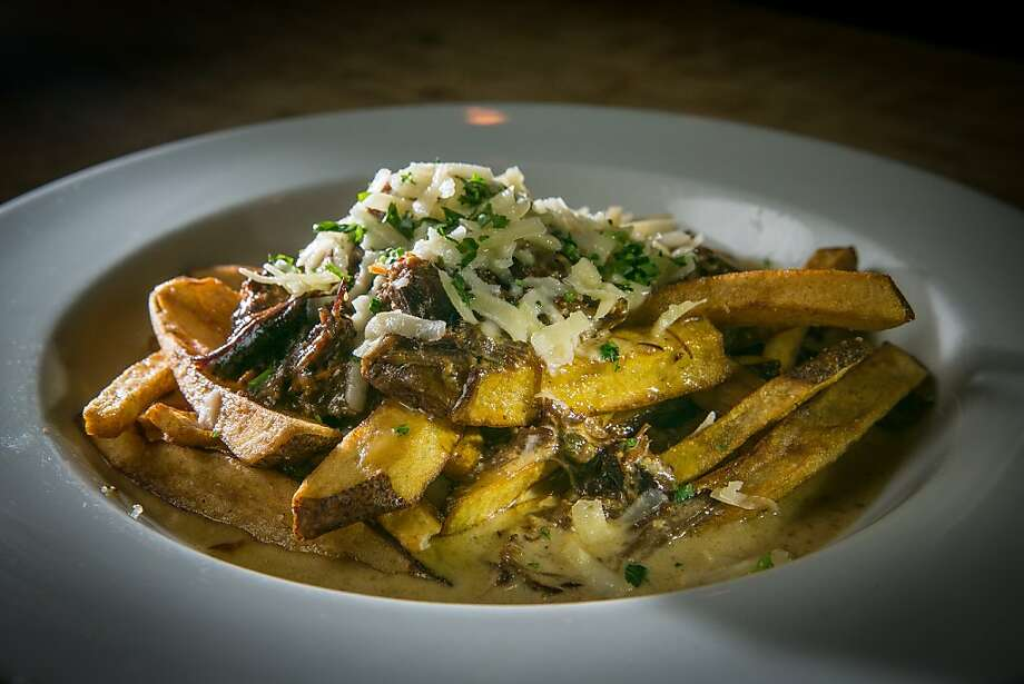 The oxtail poutine at the Chop Bar in Oakland includes a plate of fries drenched in oxtail gravy and topped with Fiscalini cheddar. Photo: John Storey, Special To The Chronicle