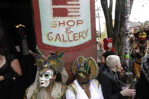 Revelers gather for the start of the Society of Saint Anne walking parade in the Bywater section of New Orleans during Mardi Gras day.  FEMA markings from Hurricane Katrina are still seen on the wall. Photo: Gerald Herbert, Associated Press / AP