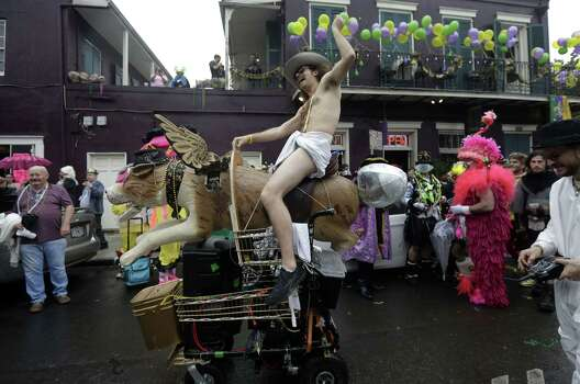 A man dressed in a diaper rides a mechanical dog with wings in the French Quarter during Mardi Gras in New Orleans. Crowds were a little smaller than recent years, perhaps influenced by the forecast of rain. Photo: Gerald Herbert, Associated Press / AP