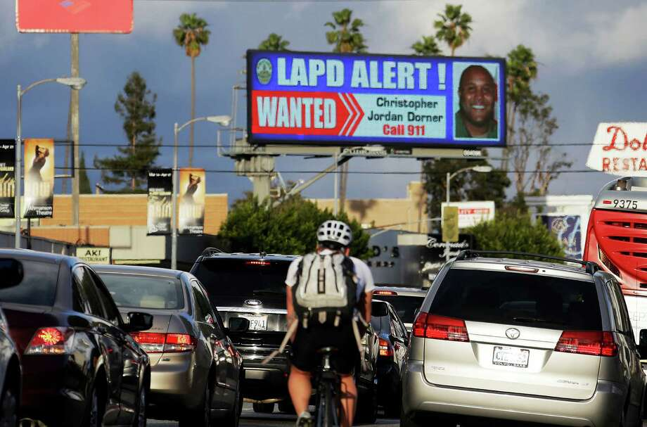 "In this Feb. 8, 2013 photo, commuters on Santa Monica Boulevard on the Westside of Los Angeles see a digital billboard displaying a large ""wanted"" poster for former Los Angeles police Officer Christopher Dorner.  Dorner is suspected in a spree of violence as part of a vendetta against law enforcement after being fired by the department. He is also a suspect in the shooting deaths of a former LAPD captain's daughter and her fiance, and two other shootings that left an officer dead and two others wounded. Dorner's alleged killing spree hasn't just terrorized a large section of the country _ it has captured people's imagination and attention. (AP Photo/Reed Saxon) Photo: Reed Saxon, STF / AP"