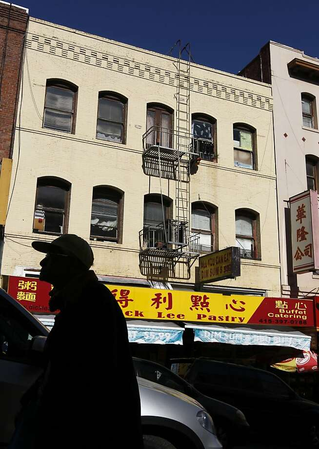 A man walks past the Dick Lee Pastry restaurant owned by Peter Yu and Ada Chu on Jackson Street in San Francisco, Calif. on Tuesday, Feb. 12, 2013. City Attorney Dennis Herrera has ordered the couple to pay $525,000 in back wages to several employees of the restaurant after forcing them to work long hours at below minimum wage. Photo: Paul Chinn, The Chronicle