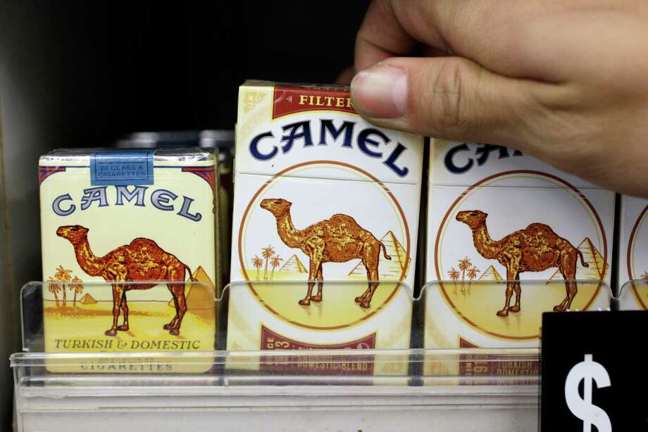 In this Feb. 1, 2011 photo, Reynolds American Camel cigarettes appear on display with the new logo shown in center and right and older logo shown at left, at a liquor store in Palo Alto, Calif. Reynolds reports earnings, Tuesday, Feb. 12, 2013. (AP Photo/Paul Sakuma) Photo: Paul Sakuma