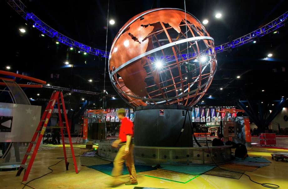 A crew prepares a globe at the George R. Brown Convention. Photo: Cody Duty / © 2013 Houston Chronicle