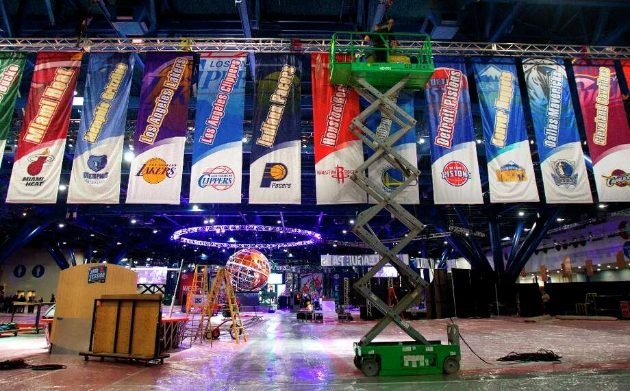 A crew member hangs banners representing each NBA team at the George R. Brown Convention Center on Tuesday. Photo: Cody Duty / © 2013 Houston Chronicle