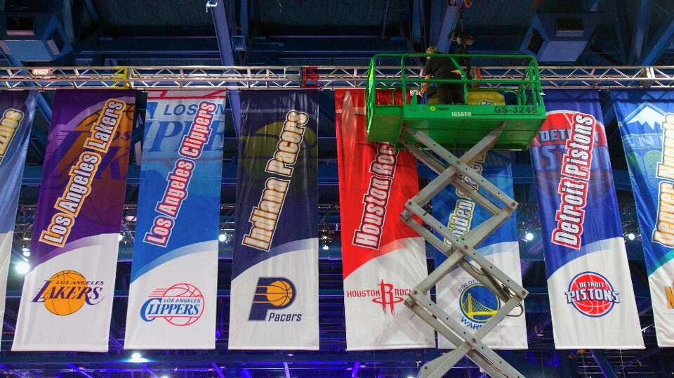 A crew member hangs banners representing each NBA team at the George R. Brown Convention Center on T
