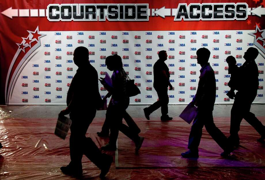 People walk the George R. Brown Convention Center as crews prepare for the NBA All-Star Jam Session. Photo: Cody Duty / © 2013 Houston Chronicle