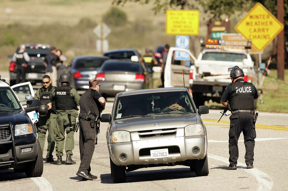 Police stand at a road block at Hwy. 38 and Bryant Street just north of Yucaipa, Calif. as a gunfight between police and fugitive ex-Los Angeles cop Christopher Dorner takes place farther up the highway in the Seven Oaks community, Tuesday, Feb. 12, 2013. (AP Photo/The Press-Enterprise, Stan Lim)  NO SALES; MAGS OUT; MANDATORY CREDIT Photo: Stan Lim, AP / The Press-Enterprise