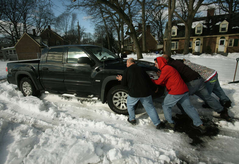 Forest Court neighbors push a stranded vehicle from their street that they banded together to cle