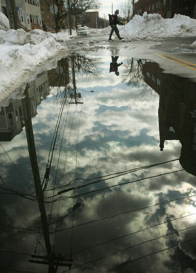 Melting snow forms an enormous reflecting puddle on Lafayette Boulevard in Bridgeport, Conn. on Tues