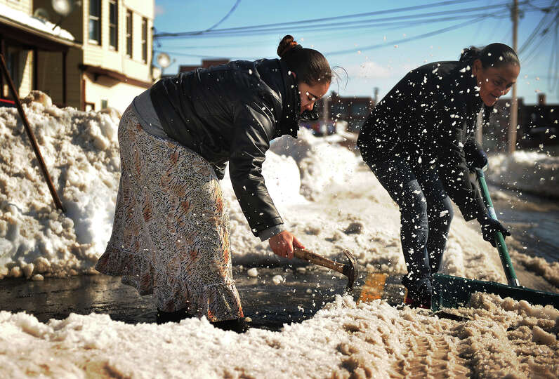 Isaura Pimental, left, and Eddie Perez, both of Bridgeport, use a hammer and shovel to hack away at