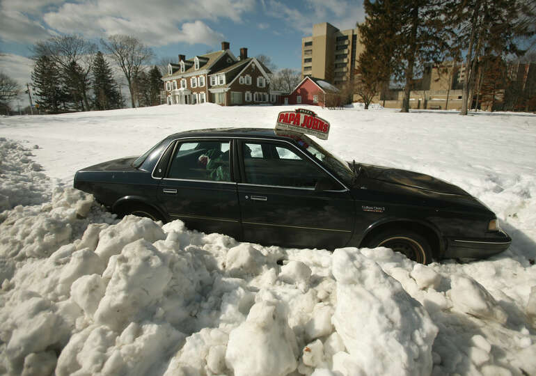 A pizza delivery car is stranded in the snow off Waldemere Avenue in Bridgeport, Conn. on Tuesday, F