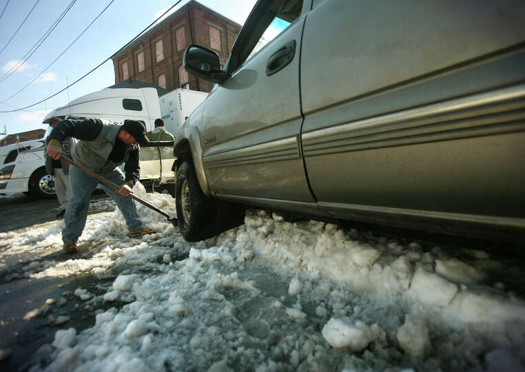 Pedro Quintero of Bridgeport digs out his stranded pickup truck on Barnum Avenue in Bridgeport on Tu