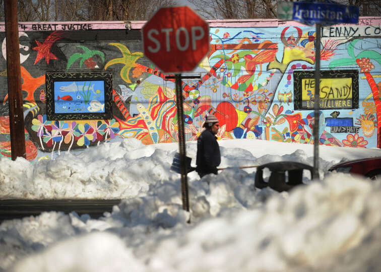 A building makes a colorful contrast to the piles of snow along Iranistan Avenue in Bridgeport, Conn