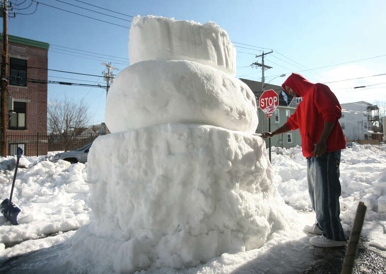 Tony Keene carves a giant snowman along Maplewood Avenue in Bridgeport, Conn. on Tuesday, February 1