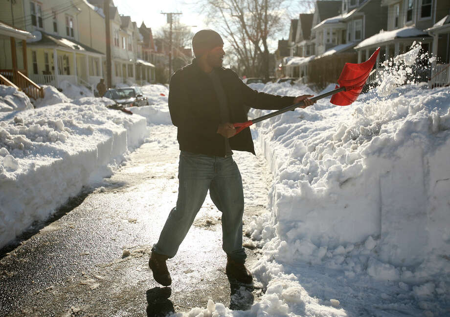 Joshua Walker bands together with his neighbors to shovel snow on Hazelwood Avenue in Bridgeport, Conn. on Tuesday, February 12, 2013. Photo: Brian A. Pounds / Connecticut Post