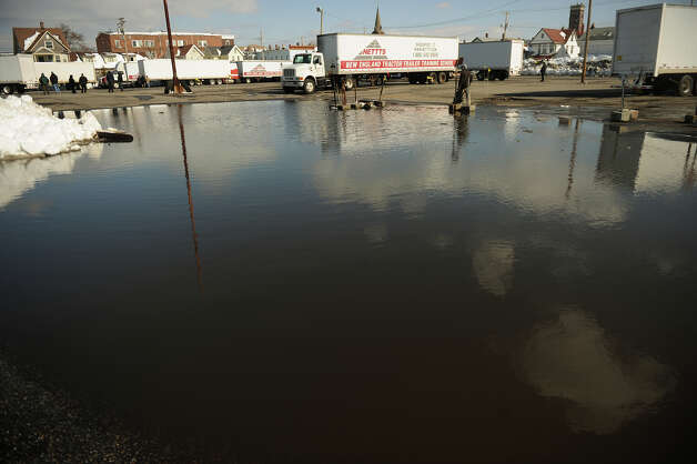 Melting snow creates an enormous puddle in a parking lot off Barnum Avenue in Bridgeport, Conn. on Tuesday, February 12, 2013. Photo: Brian A. Pounds / Connecticut Post
