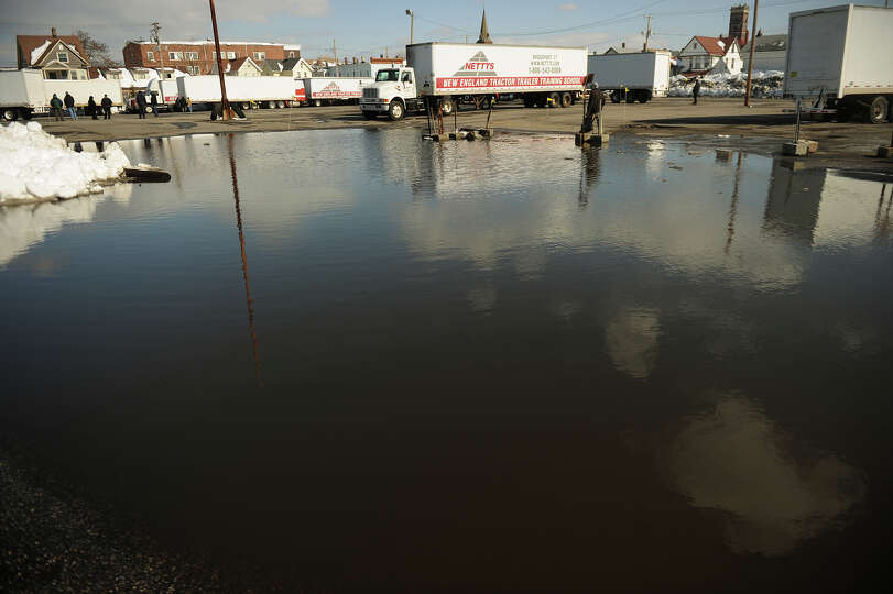 Melting snow creates an enormous puddle in a parking lot off Barnum Avenue in Bridgeport, Conn. on T