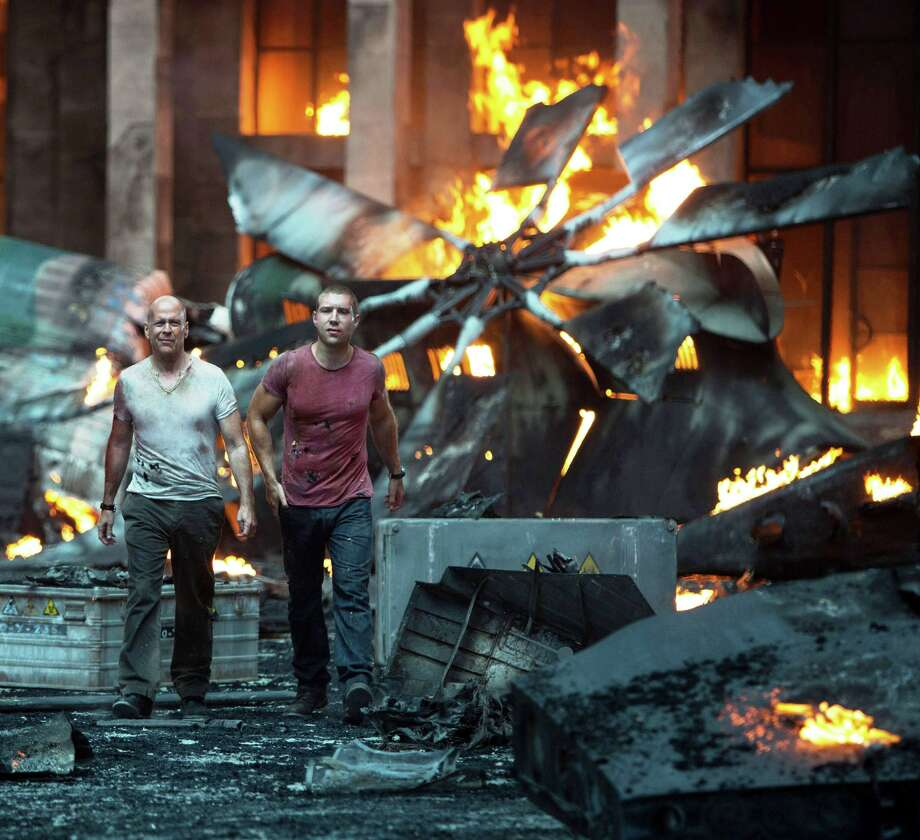 "John McClaine (Bruce Willis) and his son Jack (Jai Courtney) survey the wreckage after their encounter with assassins in ""A Good Day to Die Hard."" Photo: 20th Century Fox"