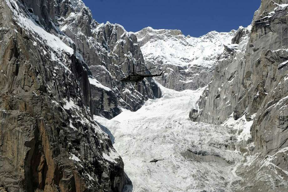 A Pakistan Army helicopter (top) carrying President Asif Ali Zardari, Army Chief General Ashfaq Kayani, and other officials fly over the site of an avalanche over Gayari camp near the Siachen glacier on April 18, 2012. Rescuers are still searching for nearly 140 soldiers buried by the mass of snow and rock at Gayari camp near the Siachen glacier, 4,000 metres above sea level. More than 450 rescuers are working at the site near the de facto border with India in the militarised region of Kashmir, though experts have said there is virtually no chance of finding any survivors. (AAMIR QURESHI/AFP/Getty Images) Photo: AAMIR QURESHI, Multiple / 2012 AFP
