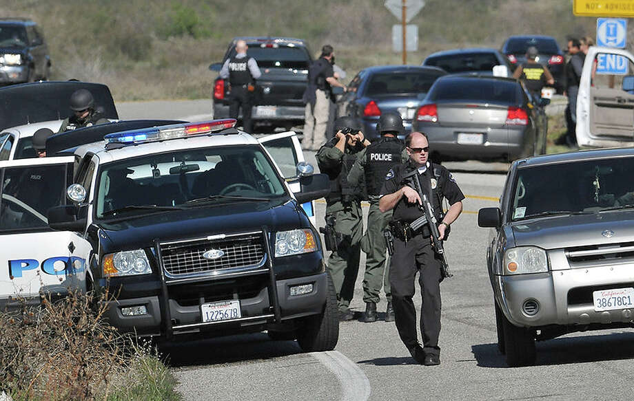 Redlands Police officers man a blockade  near the entrance to the San Bernardino National Forest in southern California after Christopher Dorner, a fugitive ex-Los Angeles cop sought in three killings, engaged in a shootout with authorities that wounded two officers in the San Bernardino Mountains near Big Bear Lake, Tuesday, Feb. 12, 2013. Photo: Gabriel Luis Acosta, AP / San Bernardino Sun