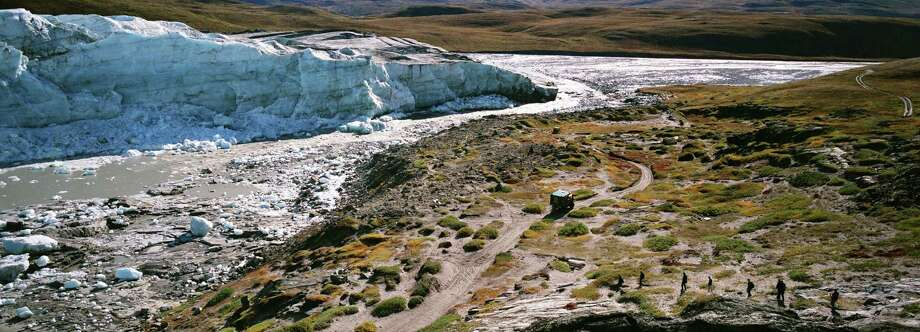 Tourists walk by the Russell Glacier, September 01, 2007 , Greenland. Scientists believe that Greenland, with its melting ice caps and disappearing glaciers, is an accurate thermometer of global warming. (Photo by Uriel Sinai/Getty Images) Photo: Uriel Sinai, Multiple / 2007 Getty Images