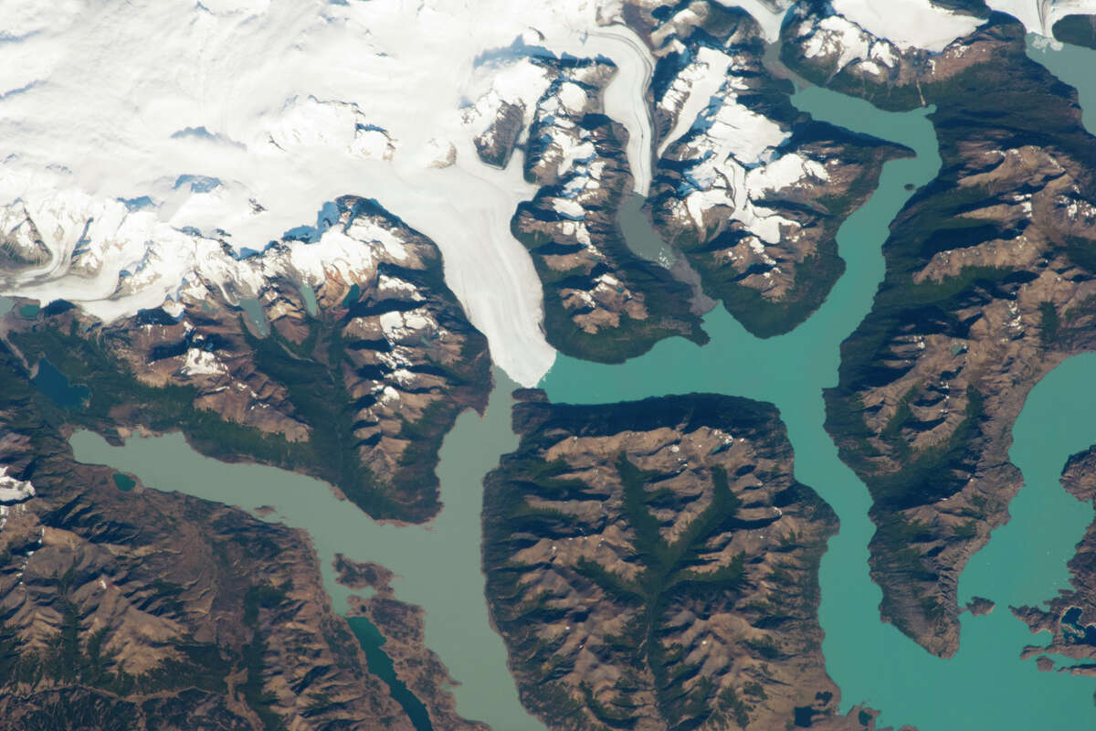 From NASA : The Perito Moreno Glacier is one of the largest in Patagonia. The glacier descends from the Southern Patagonian Icefield (image top) - 6825 feet elevation in the Andes Mountains - down into the water and warmer altitudes of Lago Argentino. (Note: In this photograph from astronauts on the International Space Station, the image is rotated so that north is to the right.) Perito Moreno is perhaps the region's most famous glacier because it periodically cuts off the major southern arm (known as Brazo Rico) of Lake Argentino. The glacier advances right across the lake until it meets the opposite shoreline, and the ice tongue is