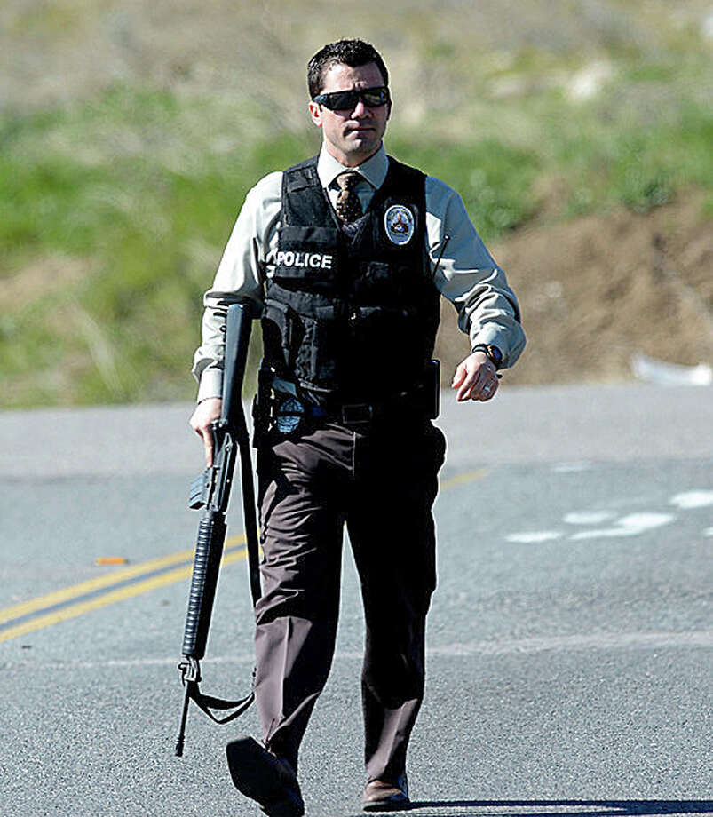 A Redlands Police officer walks near a road blockade near the entrance to the San Bernardino National Forest in southern California after Christopher Dorner, a fugitive ex-Los Angeles cop sought in three killings, engaged in a shootout with authorities that wounded two officers in the San Bernardino Mountains near Big Bear Lake, Tuesday, Feb. 12, 2013. Photo: Gabriel Luis Acosta, AP / San Bernardino Sun
