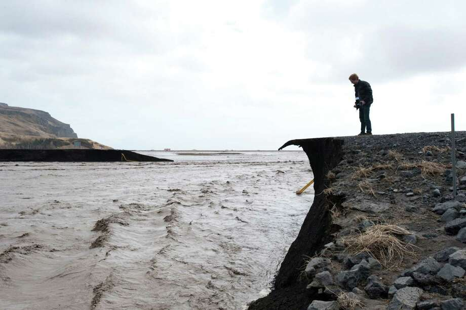 A man takes a picture of a road that has been washed away by flood water following the melting of the Eyjafjallajokull glacier due to the eruption of a volcano on April 14, 2010 near Reykjav�k. Iceland's second volcano eruption in less than a month melted part of a glacier and caused heavy flooding yesterday, forcing up to 800 people to evacuate and grounding flights. (HALLDOR KOLBEINS/AFP/Getty Images) Photo: HALLDOR KOLBEINS, Multiple / 2010 AFP