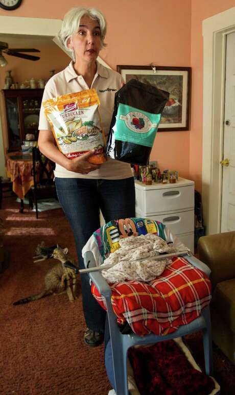 Nadine Joli-Coeur with Natural Pawz delivers dog and cat food to Alice Lewis for Meals on Wheels for Pets, n Wednesday, Jan. 30, 2013, in Houston.    ( Karen Warren / Houston Chronicle ) Photo: Karen Warren, Staff / © 2013 Houston Chronicle