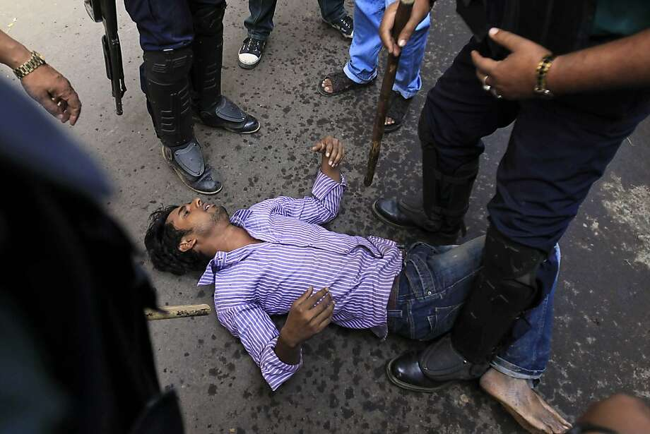 Policemen and government supporters beat a Jamaat-e-Islami activist on a Dhaka street during a demonstration by Bangladesh's largest Islamic party against the conviction of its leader. Photo: A.M. Ahad, Associated Press