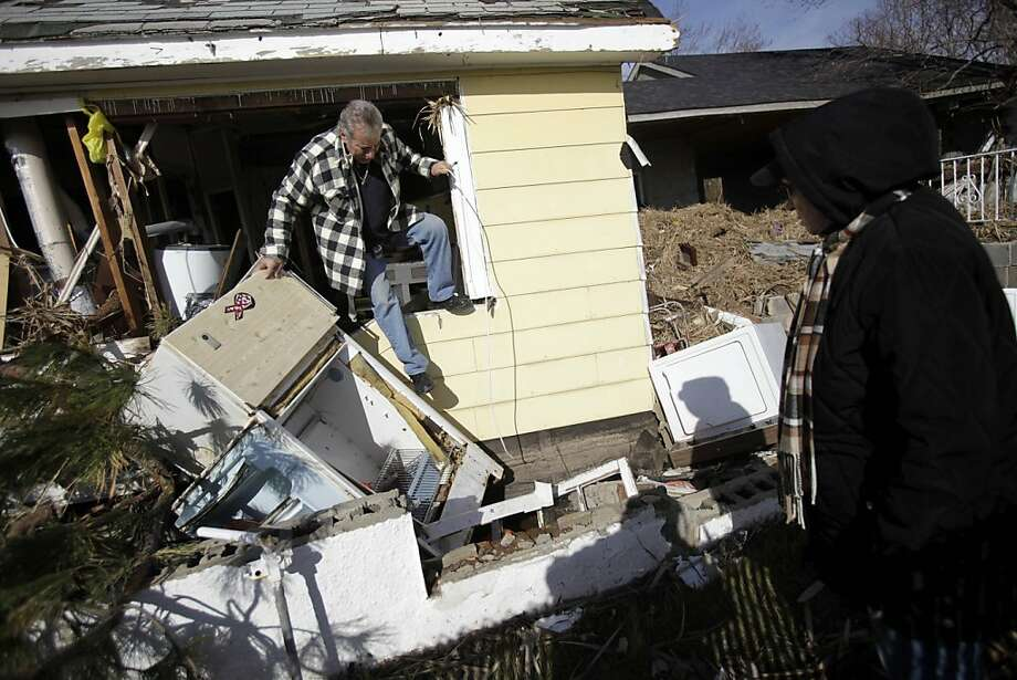 Joe Vanvaketis is watched by wife, Inez, as he climbs out of his home in Staten Island, N.Y., severely damaged by Superstorm Sandy, after trying to recover personal items. Photo: Seth Wenig, Associated Press