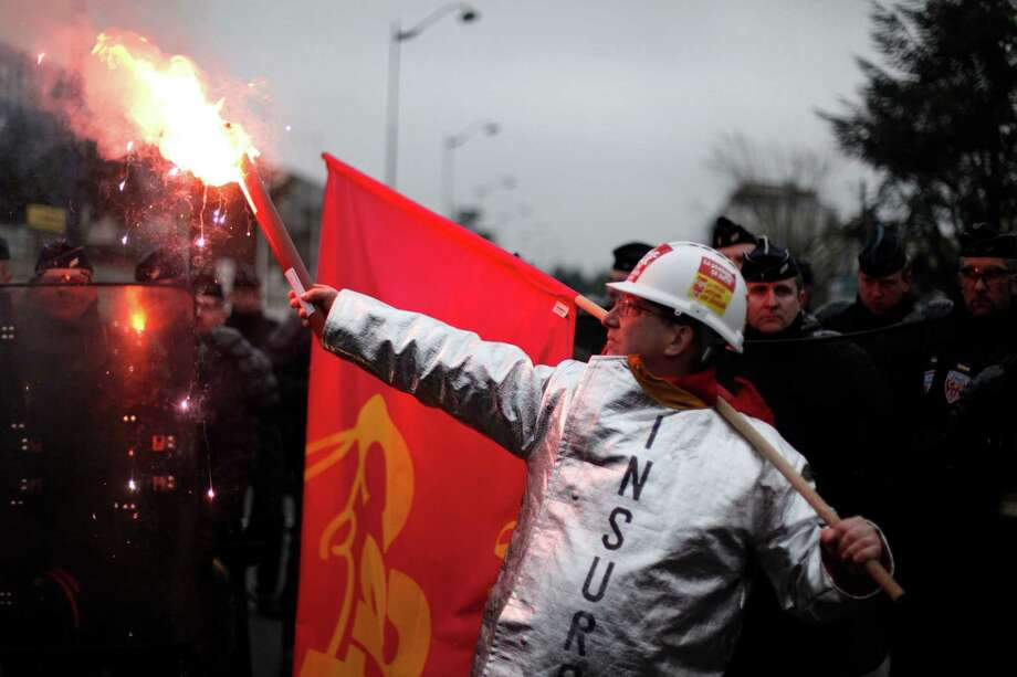 A worker of tire manufacturer Goodyear holds a flare as he faces French riot police during a demonstration in front the Goodyear headquarters, in Reuil Malmaison, outside Paris, Tuesday Feb. 12, 2013. U.S. tyremaker Goodyear confirmed in January to close a French plant near the northern city of Amiens, which would lead to the layoff of 1,173 jobs. (AP Photo/Thibault Camus) Photo: Thibault Camus, STR / AP