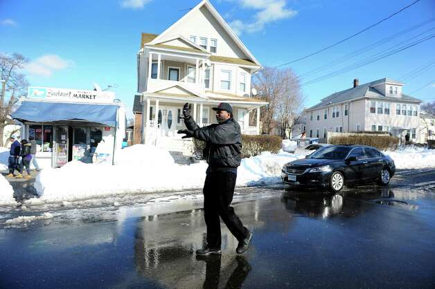Resident Jesse Wright helps direct the flow of traffic on Beechmont Avenue in Bridgeport, Conn. which was reduced to one lane following the heavy weekend snow fall  Tuesday, Feb. 12, 2013. Photo: Autumn Driscoll