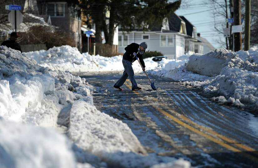 Jose Barbosa clears snow from Beechmont Avenue in Bridgeport, Conn. which was reduced to one lane fo