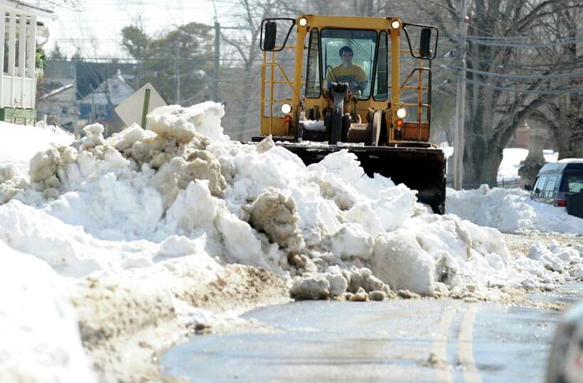 A bulldozer moves snow from Hawthorne Ave. in Derby, Conn. into a dump truck to be carted away  Tues