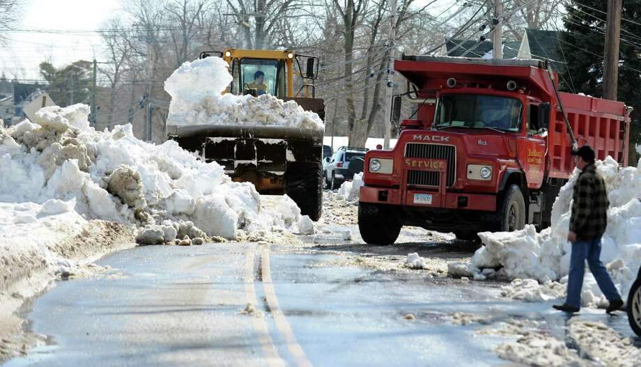 A bulldozer moves snow from Hawthorne Ave. in Derby, Conn. into a dump truck to be carted away  Tuesday, Feb. 12, 2013 following a weekend storm that dumped up to 3 feet across the state. Photo: Autumn Driscoll