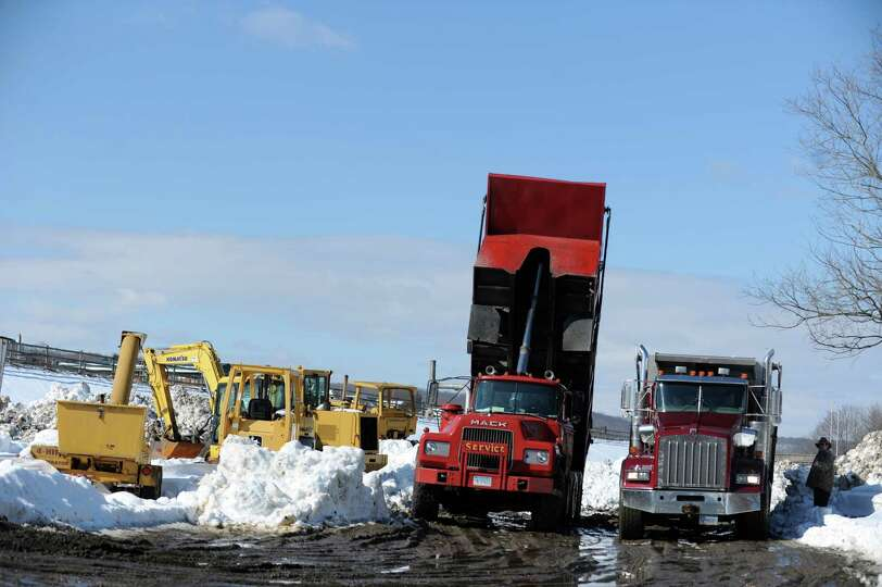 Dump trucks empty their loads of snow near the Riverwalk in Derby, Conn. Tuesday, Feb. 12, 2013 foll