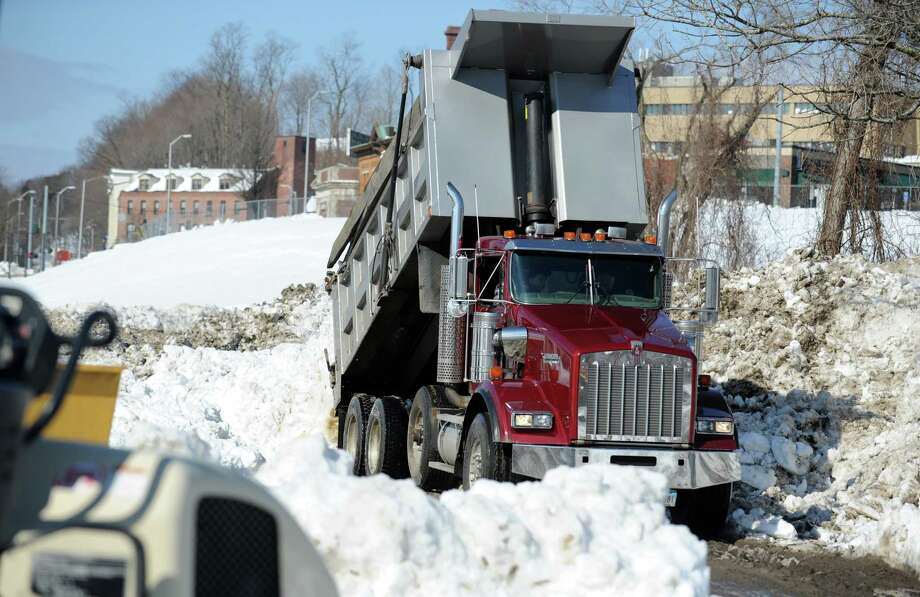 A dump truck empties its load of snow near the Riverwalk in Derby, Conn. Tuesday, Feb. 12, 2013 following a weekend storm that dumped up to 3 feet across the state. Photo: Autumn Driscoll