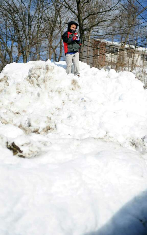 Six-year-old Bryan Selitte stands atop a snow pile where his father piled the snow from their driveway Tuesday, Feb. 12, 2013 in Ansonia, Conn. Photo: Autumn Driscoll