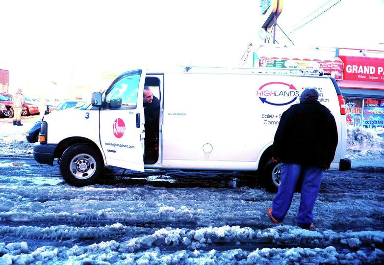 Leon Griffin stops to help a van stuck in the snow on Main Street in Bridgeport, Conn. Tuesday, Feb.