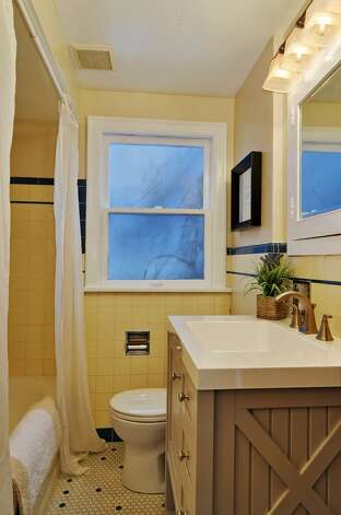 Bathroom of 121 N.W. 80th St. The 2,580-square-foot house, built in 1928, has four bedrooms, two bathrooms, built-ins, exposed-wood moldings, doors and shelves, and coved ceilings on a 4,160-square-foot lot. It's listed for $425,000, although a sale is pending. Photo: Stefen Enriquez/Courtesy Larry Crites/Lake & Co. Real Estate