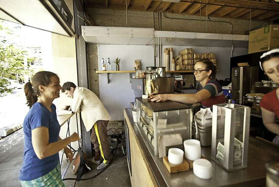 Rose Brady hands a coffee to customer Chrissy Antenucci at the Blue Bottle Coffee in Hayes Valley. The chain is beginning to accept payments via the Square Wallet mobile phone app. Square, based in San Francisco, reached a similar deal with Starbucks last year. Photo: Craig Lee, Special To The Chronicle