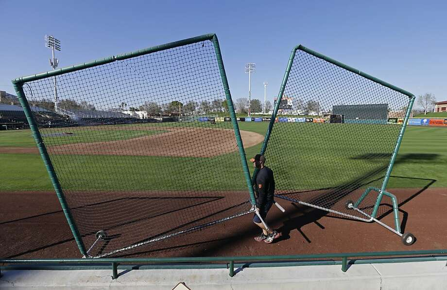 A grounds crew member at Scottsdale Stadium wheels out safety screens for the start of the San Francisco Giants spring training baseball workouts Tuesday, Feb. 12, 2013, in Scottsdale, Ariz. The pitchers and catchers for the defending World Champions start workouts on Wednesday. (AP Photo/Darron Cummings) Photo: Darron Cummings, Associated Press