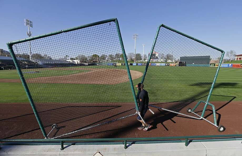 A grounds-crew member at Scottsdale Stadium wheels out safety screens for the start of the Giants' s