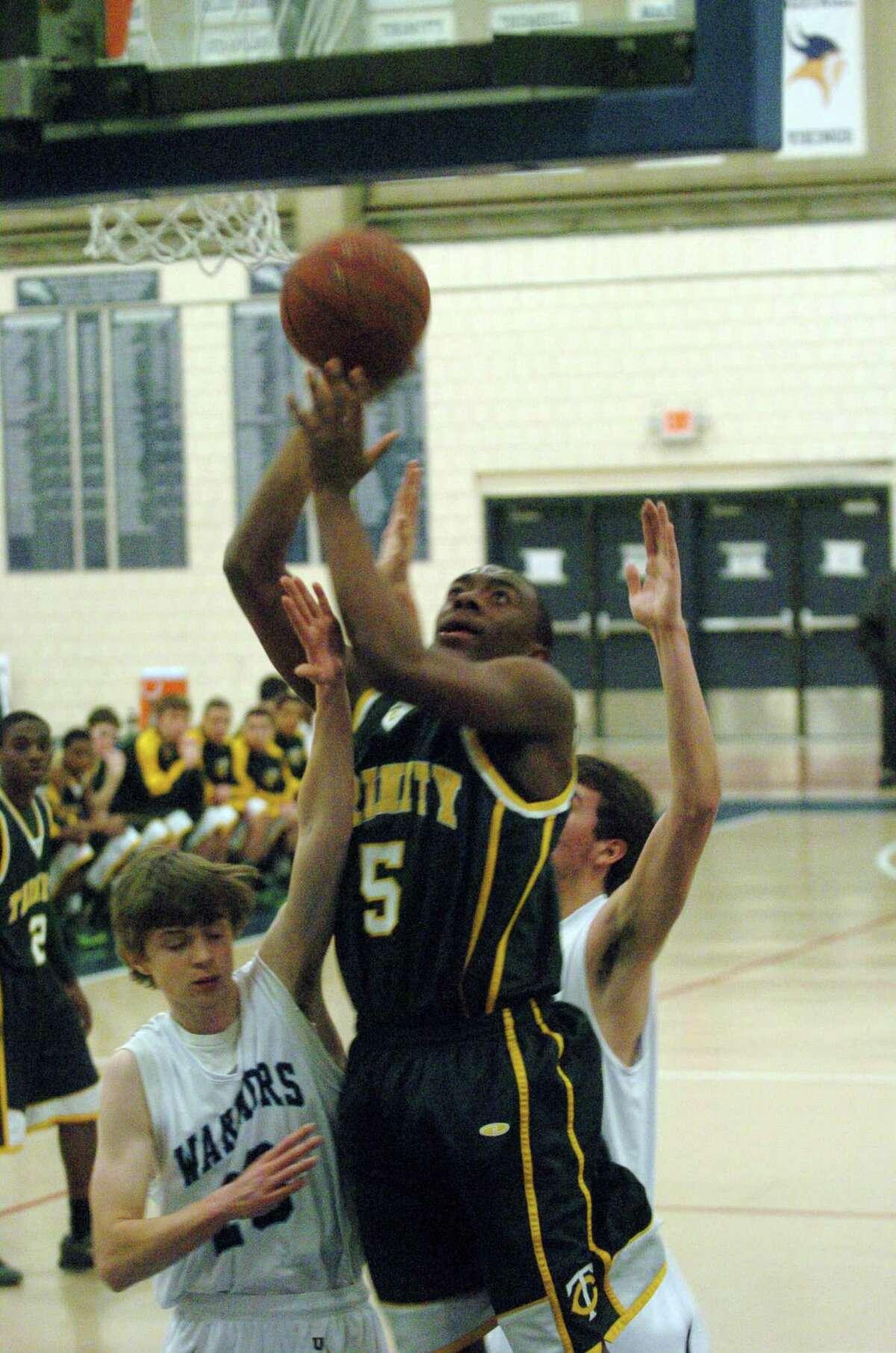 Trinity's Brandon Wheeler puts the ball up as Wilton's Chris Curtis defends as Wilton High School hosts Trinity Catholic in a boys basketball game in Wilton, Conn., Feb. 12, 2013.