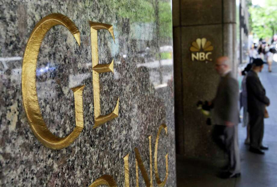 "FILE - In this file photo made July 15, 2009, General Electric and NBC logos adorn the GE Building in New York's Rockefeller Center. Comcast said Tuesday that it's buying General Electric's 49 percent stake in the NBCUniversal joint venture for $16.7 billion several years early, as the company takes advantage of low borrowing costs and what CEO Brian Roberts called a ""very attractive price."" (AP Photo/Richard Drew, File) Photo: Richard Drew"
