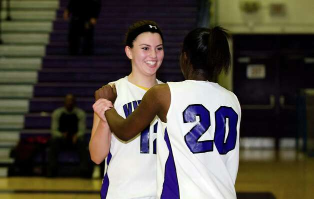 Westhill's Jackie Paasman (12), facing camera, congratulates teammate Tyler Evans (20) on a basket during the girls basketball game against New Canaan at Westhill High School in Stamford on Tuesday, Feb. 12, 2013. Photo: Amy Mortensen / Connecticut Post Freelance