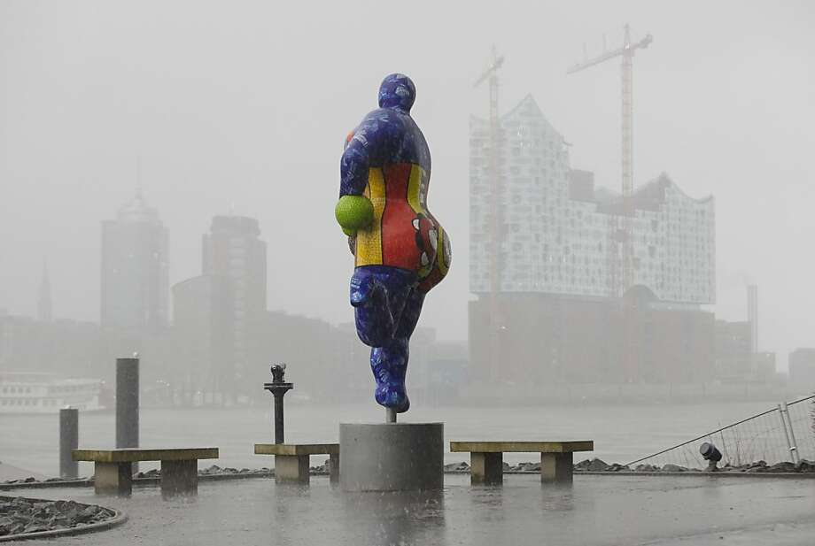 A sculpture by French artist Niki de Saint Phalle stands at the port of Hamburg in northern Germany. In the background is the Hanseatic City's philharmonic hall, the Elbphilharmonie, still under construction. Photo: Georg Wendt, AFP/Getty Images