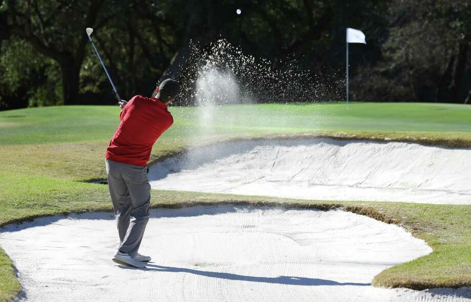 Rob Lee hits out of a bunker guarding the 18th green at Canyon Springs Golf Club. The sand traps at the course have received a new foundation that helps them drain better, thanks to a $350,000 investment from course operator Eagle Golf. Photo: Bob Owen / San Antonio Express-News