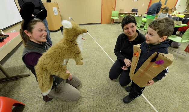 Environmental Educator Sara Poggi, left shows a fox puppet to Gabriela Sarhos and her son Pavel 3, Feb. 12, 2013, at the Pine Bush Discovery Center in Albany, N.Y.  The Sarhos' were part of a Pre-K program at the Discovery Center that teaches how our native animals survive the long, cold winters in this region.    (Skip Dickstein/Times Union) Photo: SKIP DICKSTEIN / 00021129A